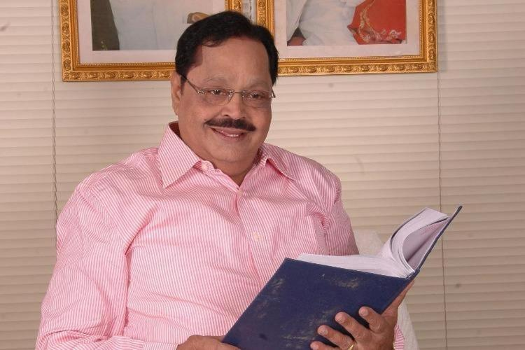 Duraimurugan wearing a pink shirt holds a book before a framed painting in the background