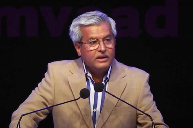 A file image of Dushyant Dave wearing a brown blazer and speaking at an event organised by Manthan foundation