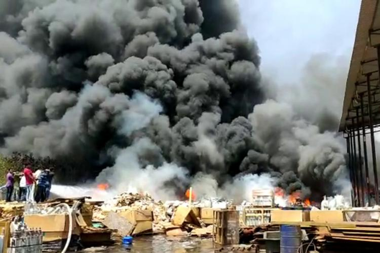 Firefighters trying to douse the flames at a scrapyard in Vizag thick black smoke is rising out of the fire