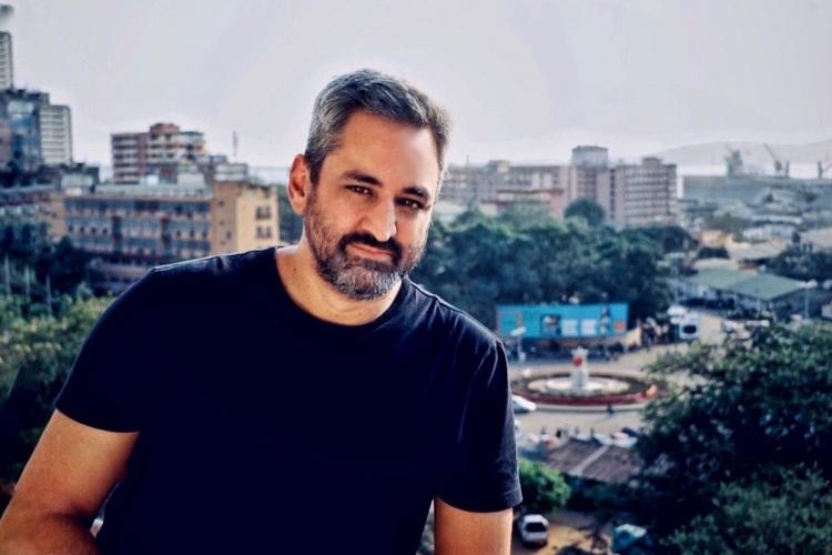 Director Dylan Mohan Gray wearing a black t-shirt and looking into the camera against the backdrop of a city