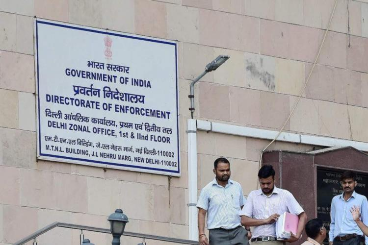 Three officials in front of the Enforcement Directorate office in New Delhi