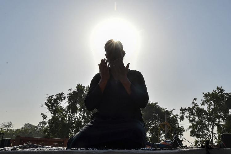 Man on knees offers prayers with both hands facing his face and eyes closed He has a skullcap and is kneeling down against the morning sun the blue sky and trees are in the background