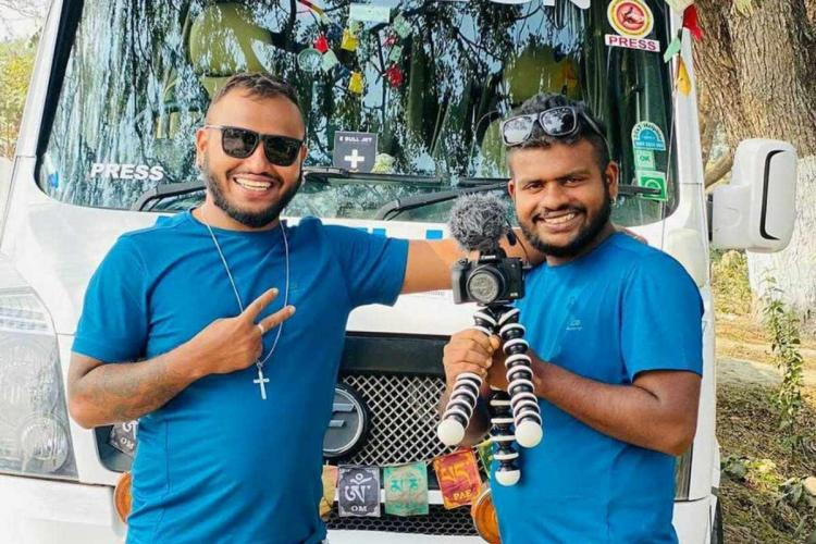 Libin and Ebin in matching blue t shirts stand next to each other in front of a white van, with sun glasses