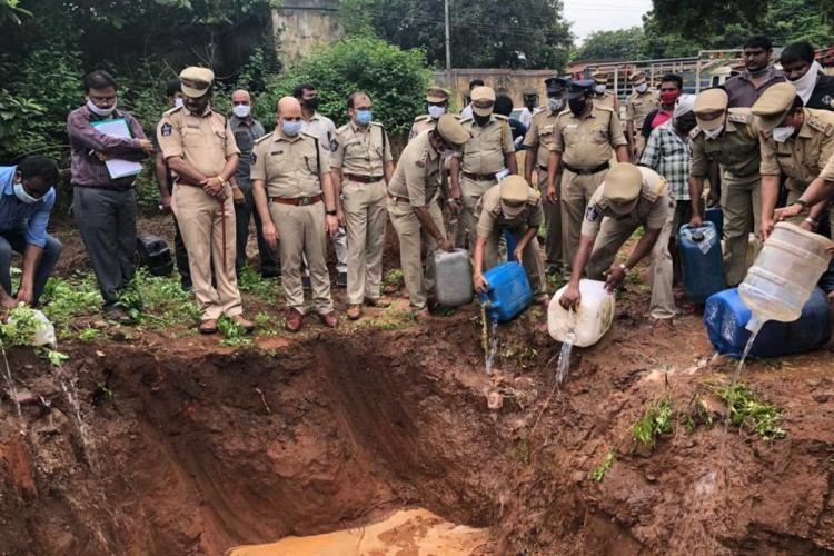 East Godavari police pouring sara or arrack distilled illegally from plastic containers into a pit