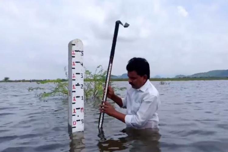 Man measuring depth of flood water in wetlands in East Godavari