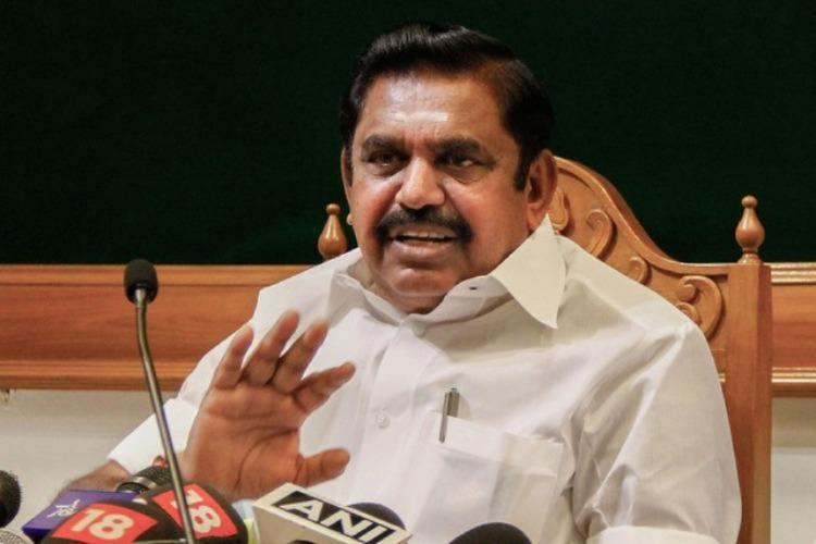 A file photo of Tamil Nadu Chief Minister Edapaddi Palaniswami during a press conference seated in front of several mics with one hand raised