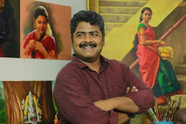 Elayaraja posing in front of his paintings