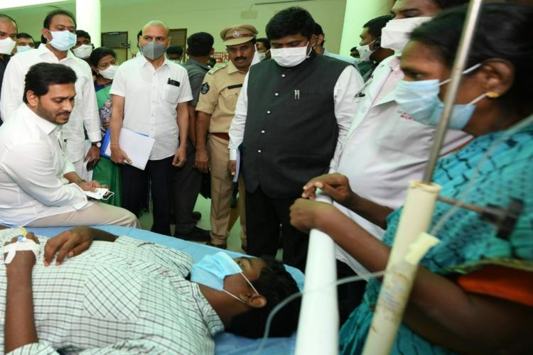 Andhra Pradesh CM Jagan Mohan Reddy sitting on the bed of a male patient hospitalised for the mysterious disease in Eluru The patients family police and other officials are seen standing beside the bed