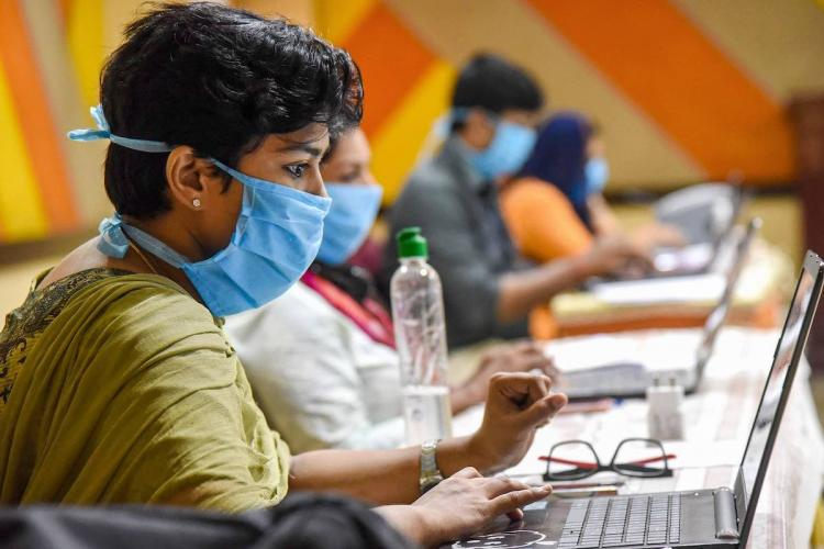 Employees of Health Tele Helpline center in Kochi wearing face masks are seen working during a nationwide lockdown