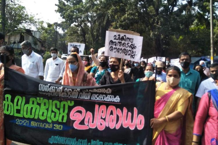 Group of people holding up banners and posters in Malayalam and protesting