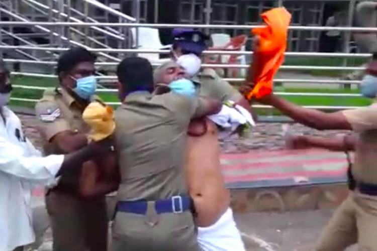 Screenshot of a man trying to wrap periyar statue in erode with a saffron coloured cloth police intervene