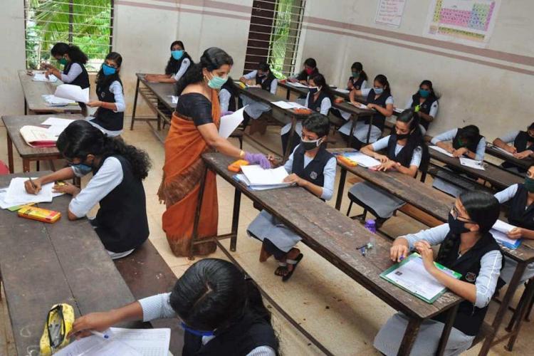 Students in a classroom writing an exam as a teacher walks around