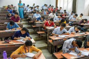 students writing exam inside classroom while a teacher inspects