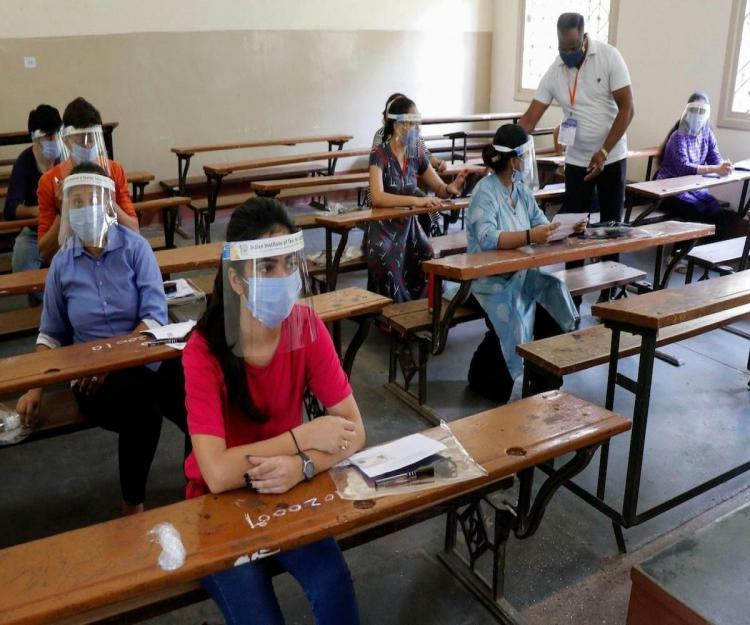 Students with face shield and masks waiting in the exam hall
