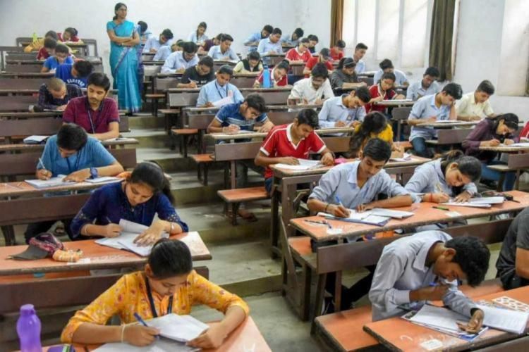 Students seen taking exams by sitting on benches one after the other with an invisilator watching them