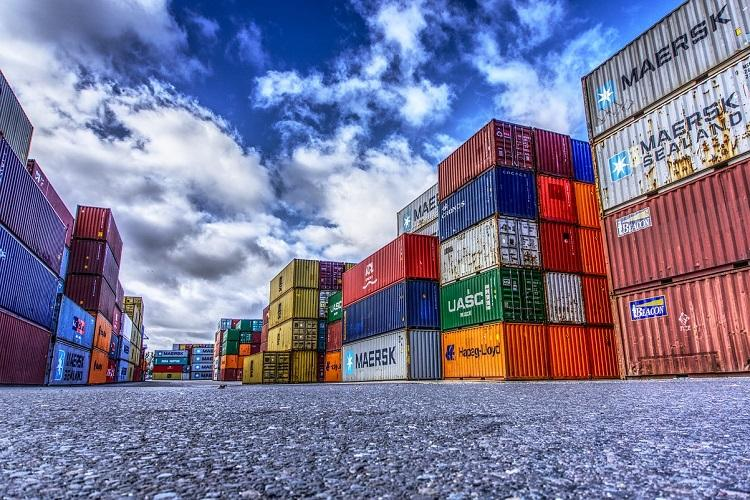 Colurful export import containers at a port against the backdrop of a blue sky to represent trade