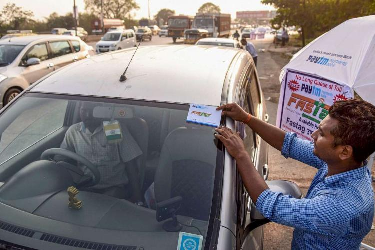 A worker fixes a FASTag sticker on the windscreen of a car. From January 1, making toll payments via FASTag will become mandatory at national as well as state highways