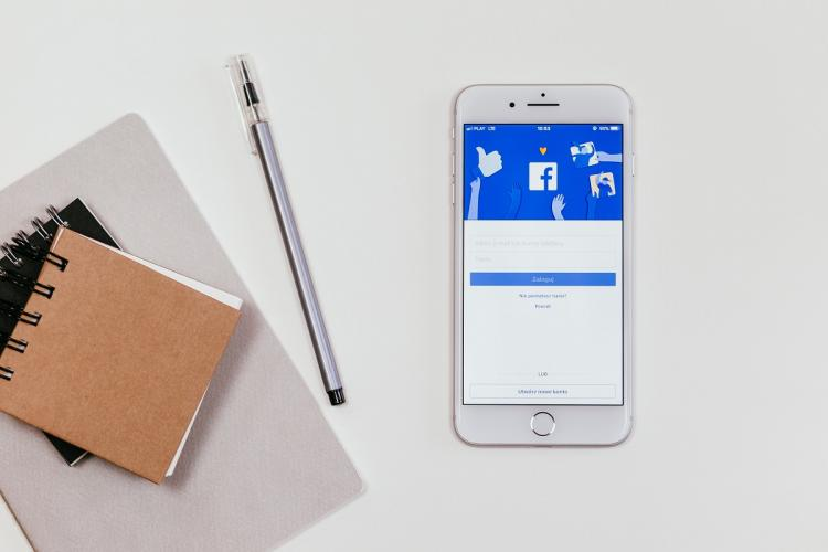 Facebook login page open on a phone next to some notepads and a pen