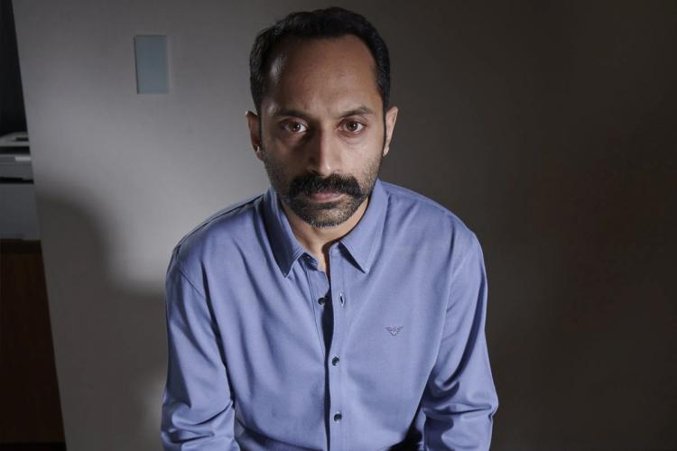 Fahadh Faasil in a blue full-sleeved shirt looking unsmiling at the camera