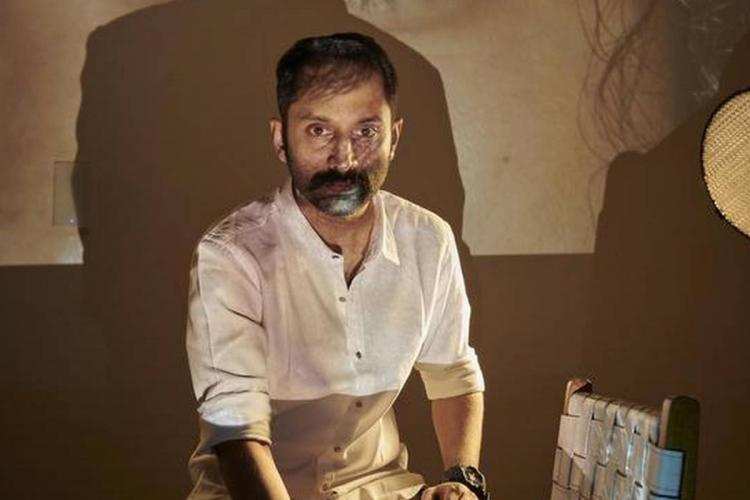 Fahadh sits wearing white in partial light, with big shadows on the wall behind him