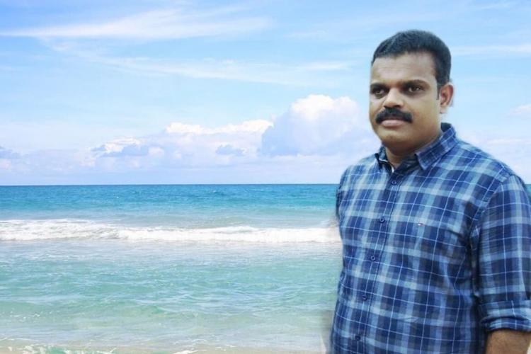 Man in deep blue shirt with thin white checks posing near a beach