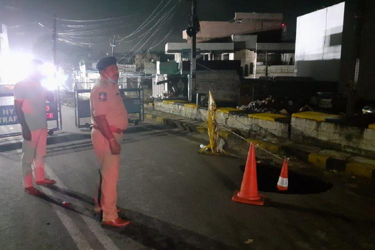 Two police personnel stand near the caved in road at Falaknuma bridge which has been shut for commuters