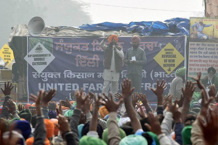 Protests being held at border, visible a sea of heads and two people standing on a stage and talking