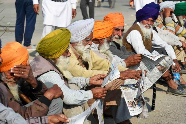 Protesting Farmers in Delhi reading the newspaper at the Singhu Border, elderly men wearing turbans of green, orange, white and blue colours are seated on the pavement while reading the papers
