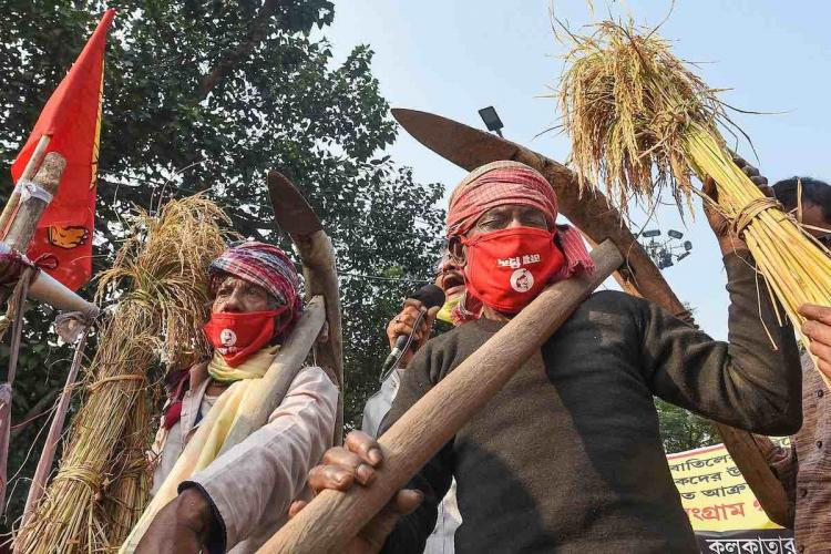 Farmers carrying their tools take part in a protest rally against the new farm laws, in Kolkata, Wednesday, Dec. 2, 2020