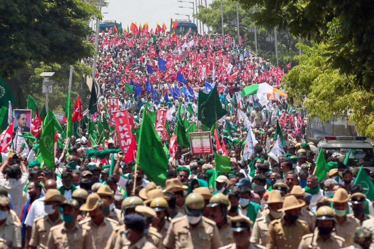 Farmers protesting holding up green and red flags in Bengaluru