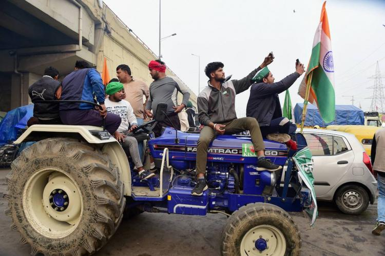 Farmers sit on a tractor with some raising their hands protesting against farm laws at Ghazipur border