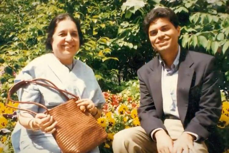Fatma Zakaria and Fareed Zakaria sit together in a garden and smile at the camera