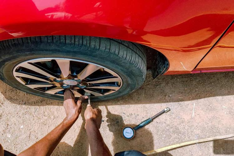 A mechanic fixes the tyre on a red car