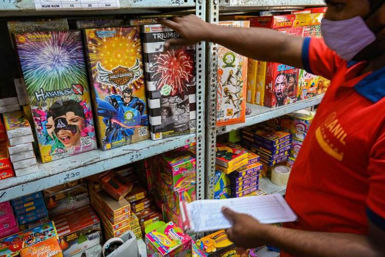 Man in red shirt pulling out a packet of fireworks in a shop