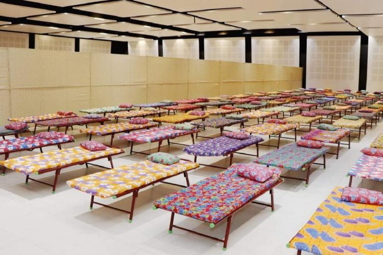 A number of beds arranged at a treatment centre with a certain distance between each other with colourful bedsheets and pillows on them