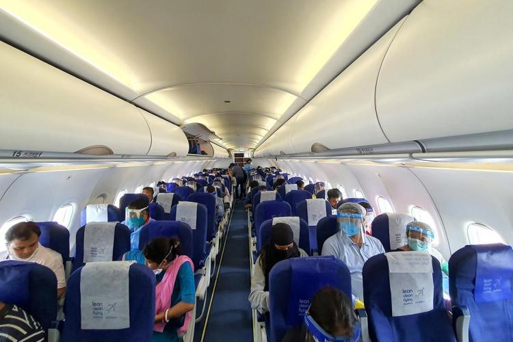 Passengers seated in a flight Many are wearing face masks and shields