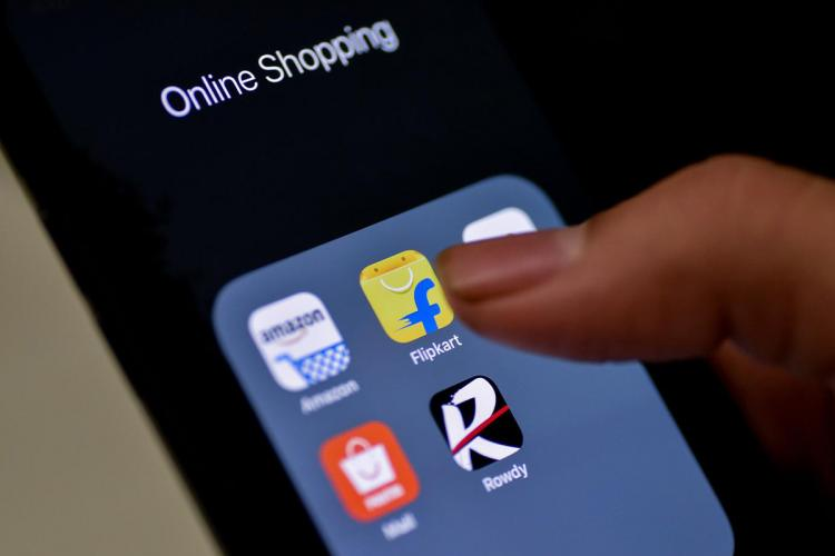 Flipkart app tile among e-commerce apps on an phone, person's finger pointing to it