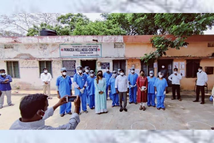 Health care workers are seen outside hospital along with others posing for a picture