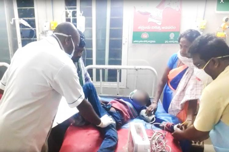 A small boy injured in the accident laying on a bed while being examined by a doctor