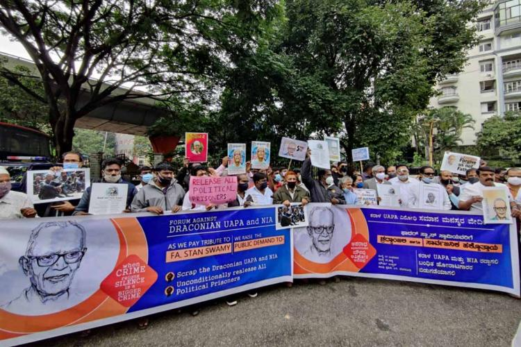 Protestors holding banner in tribute to Father Stan Swamy at Bengaluru's Maurya Circle