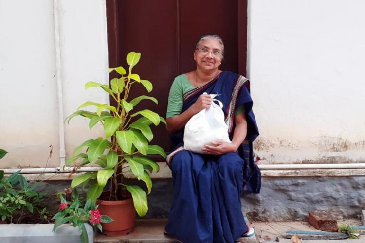 A beneficiary posing for a photograph holding the Kerala governments free food kit
