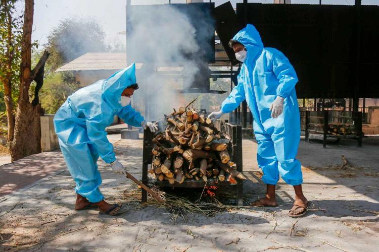 Frontline workers in personal protective equipment PPE arrange funeral pyre for Covid19 victim at a crematorium in Ahmedabad