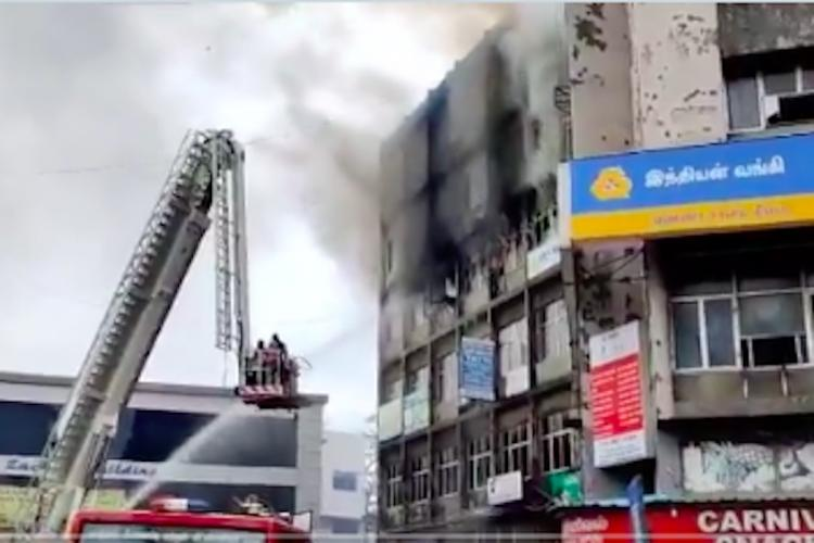 A crane placed next to a burning shopping complex