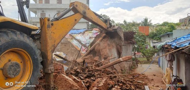 A JCB mows down a weak building in Hyderabad