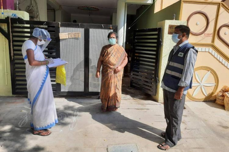 GHMC health workers conducting fever survey standing outside a womans house