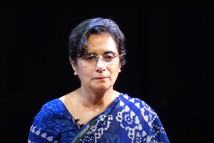 Gangandeep Kang wears a blue sari against a black background