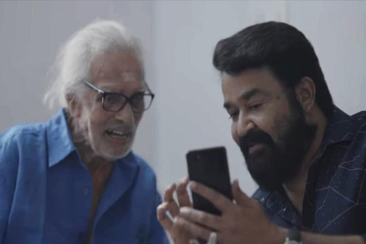 Painter Namboodiri on the left and actor Mohanlal on the right looking at the phone together.