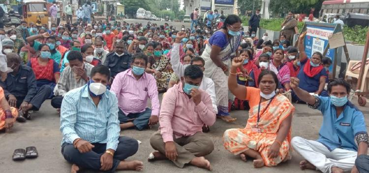 Sanitation staff comprising both men and women sitting on the road and protesting in front of Gandhi Hospital in Hyderabad