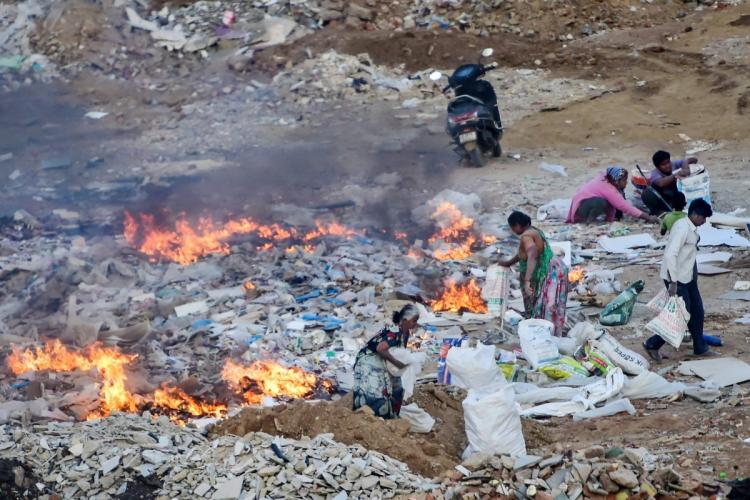 Burning of Solid Waste as some people walk through the place