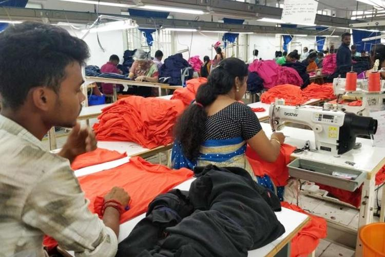 Representative image of garments workers inside factory sitting in a row and stitching clothes